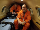 Flight Physician Justin Savage (right) aboard the Mercy Flight fixed wing aircraft, preparing for a transfer.
