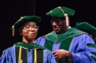 Janelle Duah is hooded by her uncle, Eric Duah, MD, before receiving her diploma.