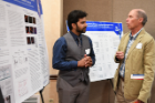 John K. Crane, MD, PhD (right), reads a poster by Muhammad B. Cheema, internal medicine resident.
