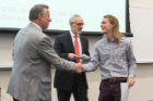 Robert Bruce shakes hands with Michael E. Cain, MD, left, after receiving his Dean's Letter of Commendation from Alan J. Lesse, MD, center.