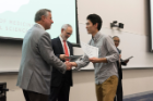 Rongjia Deng accepts congratulations from Michael E. Cain, MD, after receiving his Dean's Letter of Commendation.