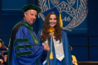 Michael E. Cain, MD, vice president for health sciences and dean of the Jacobs School, congratulates Lindsey J. Carlsen, who earned a bachelor's degree in biotechnology and an outstanding senior award in her field.