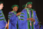 Joseph Iluore smiles as he receives his doctoral hood.