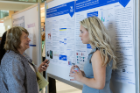 Margarita L. Dubocovich, PhD, SUNY Distinguished Professor of pharmacology and toxicology, left, listens to Hannah Zimmerman explain her research in the CLIMB Undergraduate Biomedical Informatics and Data Science program.