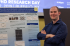 Biochemistry doctoral student Alex Sunshine stands next to his poster during the Tri-International MD-PhD Research Day at the Jacobs School.
