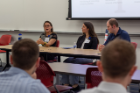 Microbiology and immunology doctoral student Mary Gallo, left, speaks during a breakout session as biochemistry doctoral student Alex Sunshine and Aimee Morris of the University of Rochester look on.