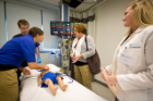 A nursing student and resident work with simulation specialists on a scenario involving an injured child and distraught parents.