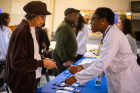 Nonye Odukwe, a first-year medical student, gives Eloise Hunter an enthusiastic welcome to the health fair.