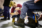 Anna Hargrave, a pre-medical student who volunteers with UB HEALS, helps lace up a client's new boots.