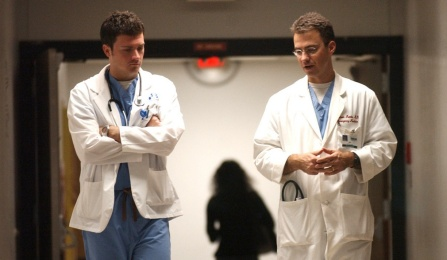 Two medical residents walking down a hospital corridor.