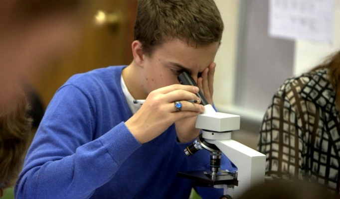 Student looking in microscope.