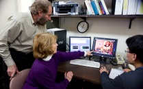 Two faculty members and a student viewing a computer screen in the Child and Family Asthma Studies Center monitoring room.
