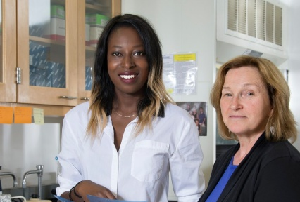 A female student in the lab, standing next to her faculty mentor.
