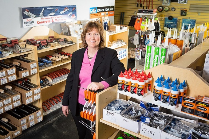 Kathy Grimm stands amid construction supplies.